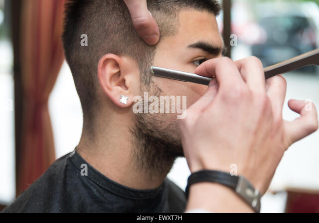 Handsome Young Hairdresser Giving A New Haircut To Male Customer At Parlor - Stock Image
