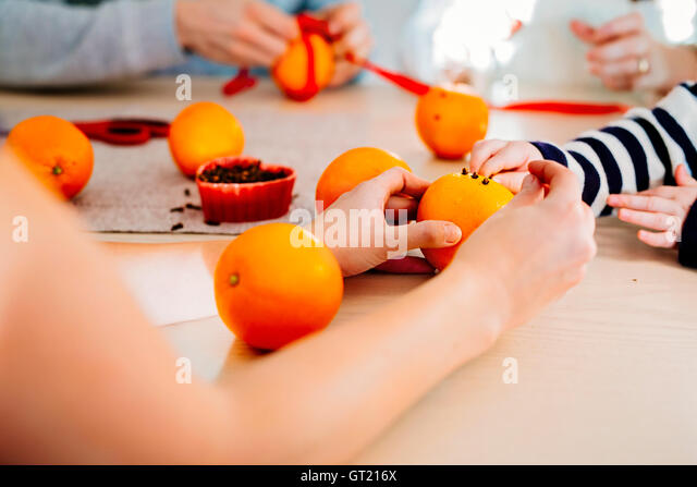 Cropped image of family preparing Christmas decorations at table - Stock-Bilder