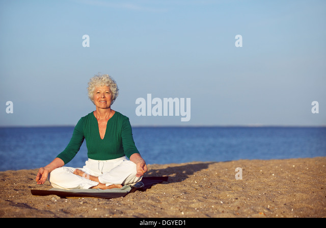 Portrait of the senior woman meditating on the seashore with lots of copyspace. Elder woman doing relaxation exercise - Stock Image