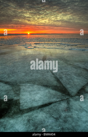 Sunrise across a frozen freshwater lake in Michigan, United States, North America with shifting ice sheets below - Stock Image