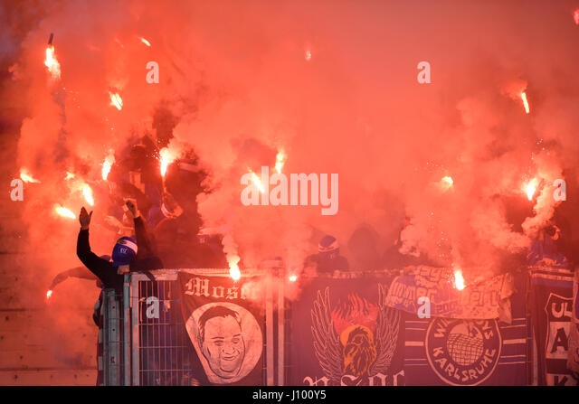 Radical fans at soccer match, hooded hooligans with Bengal light, pyrotechnics, fan section KSC Karlsruher SC - Stock Image