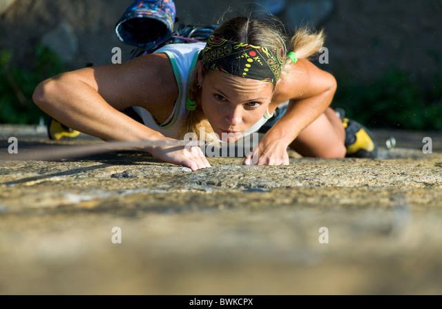 Attractive girl climbs a granite rock - Stock-Bilder