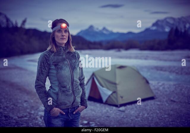 Young woman wearing headlamp, hands in pockets, looking away, Wallgau, Bavaria, Germany - Stock Image
