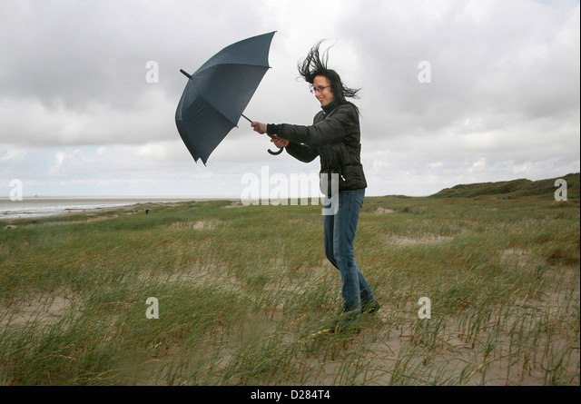 Sankt Peter-Ording, Germany, a woman is walking in wind and rain on the beach - Stock-Bilder