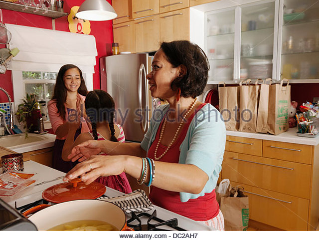 Mother and daughters in kitchen - Stock-Bilder