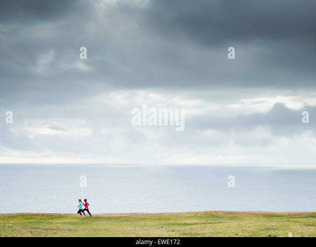 Two women jogging along the coast runners - Stock Image