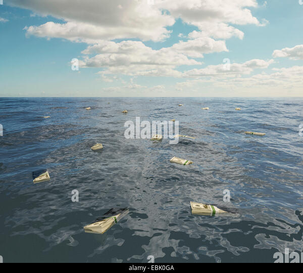Large group of one hundred dollar bill stacks floating on surface of sea - Stock Image