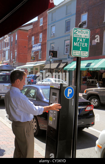 New Hampshire Portsmouth Market Street businesses pay meter parking man using - Stock Image