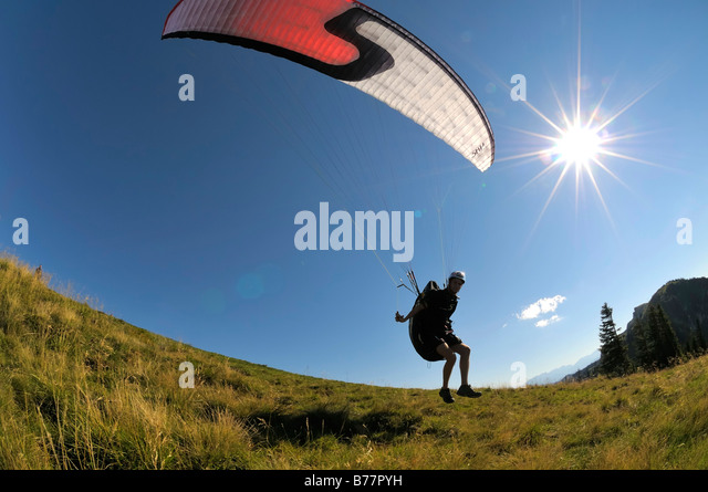 Paraglider taking off, backlit, wide-angle shot, Brauneck, Upper Bavaria, Germany, Europe - Stock Image