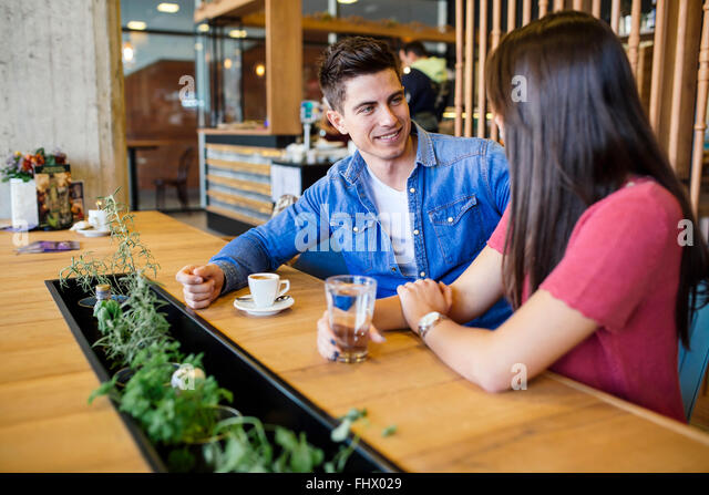 Happy young couple in restaurant waiting for food and talking - Stock-Bilder