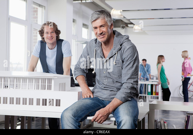 Germany, Bavaria, Munich, Men with architectural model in office, colleagues talking in background - Stock Image