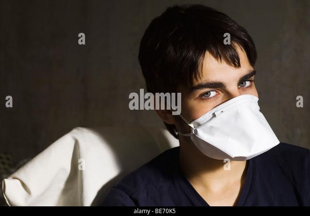 Teenage boy wearing flu mask, looking at camera - Stock Image