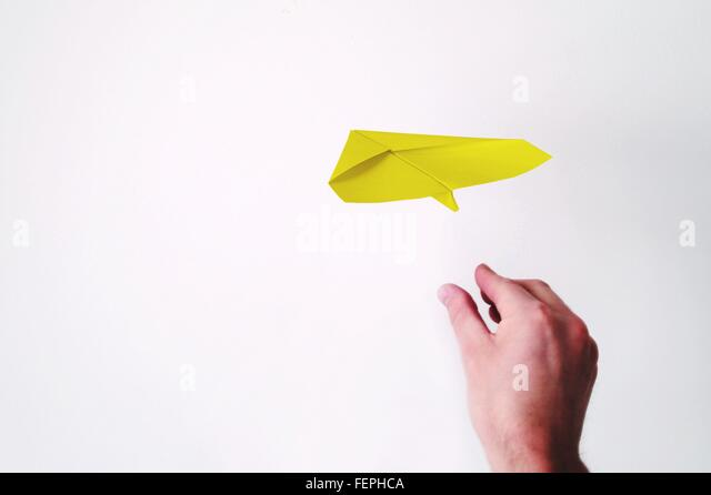 Cropped Hand Throwing Paper Airplane Against White Background - Stock Image