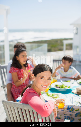 Family eating lunch at table on sunny patio overlooking ocean - Stock Image