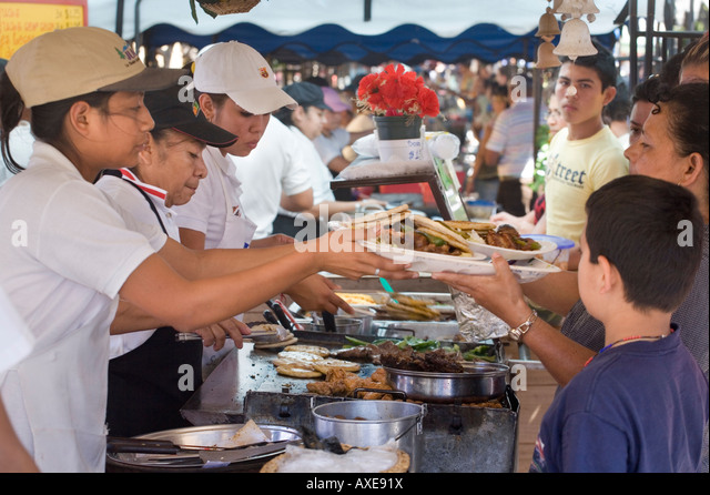 Women cooking for crowds at weekly food festival aka food fair, or feria gastronomica, Juayua, El Salvador - Stock Image