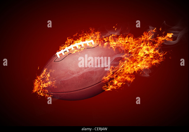 American football ball in fire isolated on dark red background - Stock Image