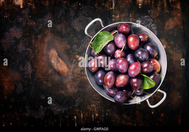Plums in a bowl on a rural background. Fresh bio fruits - Stock Image