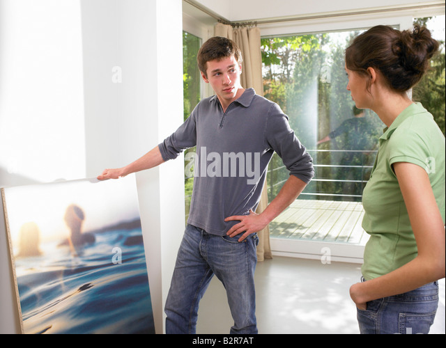 Couple hanging a painting - Stock-Bilder