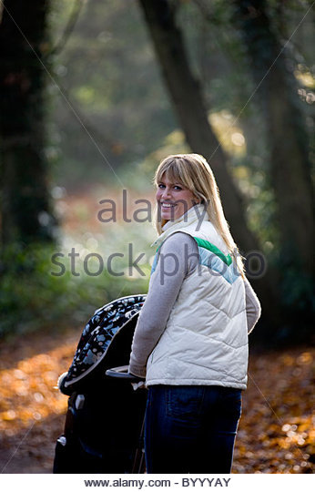 A young mother pushing a stroller in the park, smiling - Stock Image