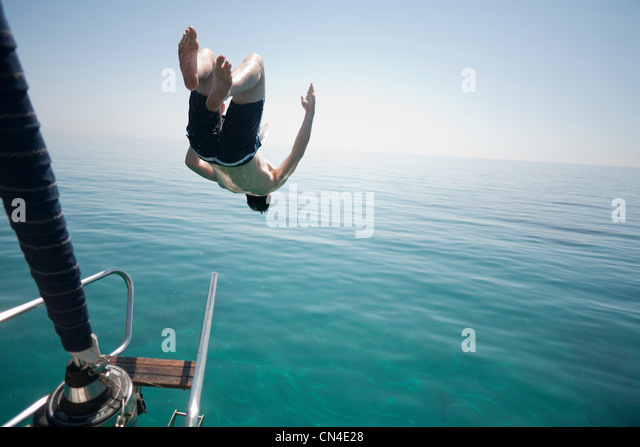 Man jumping head first into the sea - Stock Image