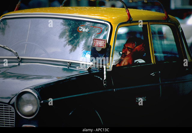A taxi driver in Mumbai India waits for a fare - Stock Image