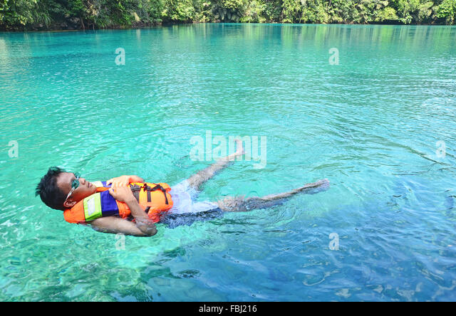 A boy floating in Labuan Cermin Lake - Stock Image