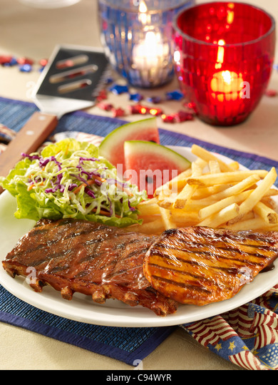 Barbecue pork ribs and chicken served with coleslaw, french fries and watermelon in a Fourth of July setting - Stock Image