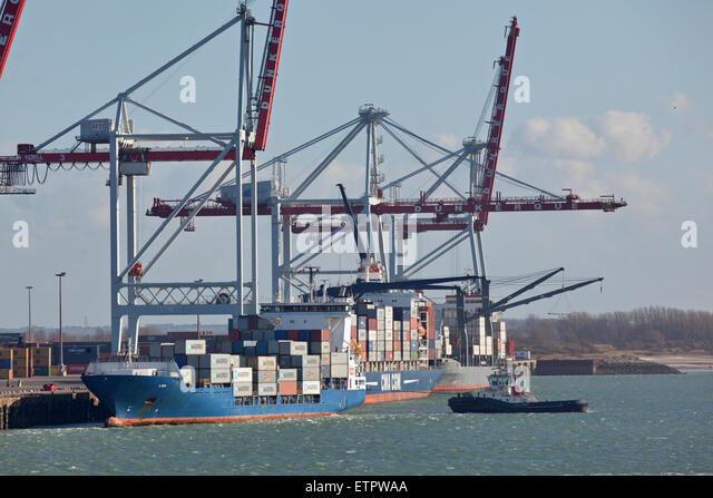 Tug boat assisting container ship by leaving Dunkirk Harbour - Stock Image