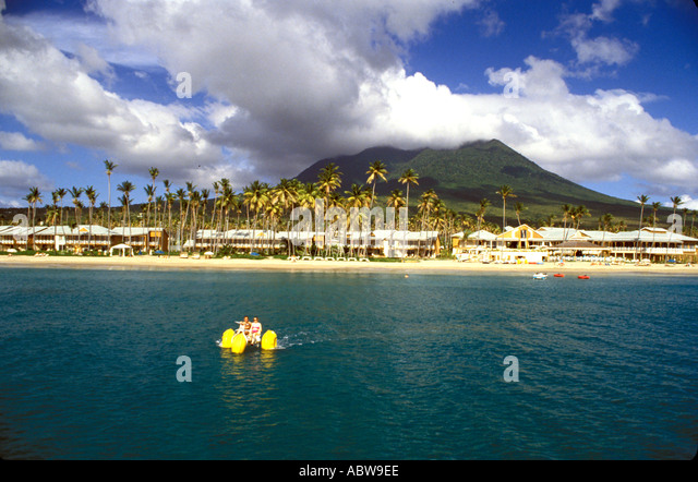 NEVIS Couple on Water Bike pedal boat Mount Nevis beach palm trees in background caribbean active watersports - Stock Image