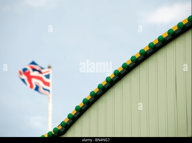 union jack flag behind green wall - Stock Image