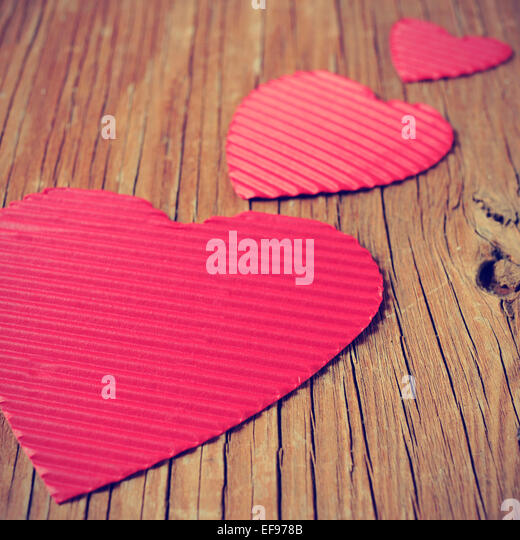 some red hearts of different sizes on a rustic wooden surface, with a filter effect - Stock Image