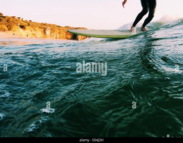 Surfer on a longboard at sunset in the summer - Stock Image