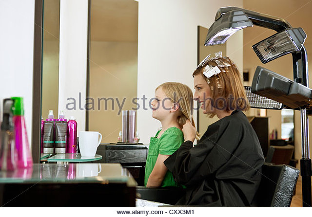 Mother and daughter looking in the mirror in a hairdressing salon - Stock Image