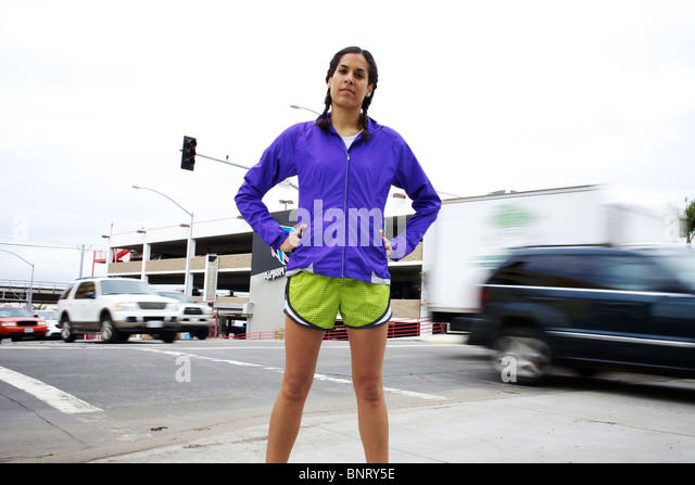 A female runner stands on the corner of two streets and cars pass by in the background creating motion blur in San - Stock Image