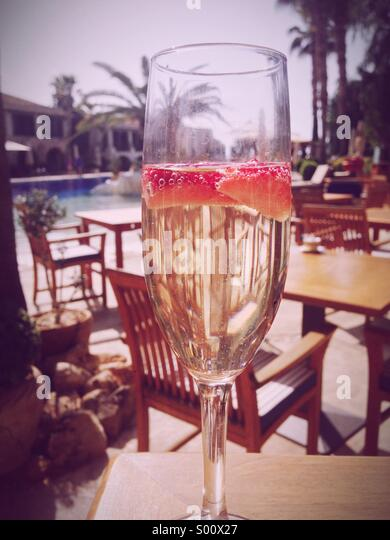 Champagne and strawberries at breakfast on a Cyprus poolside holiday resort with palm tree - Stock-Bilder
