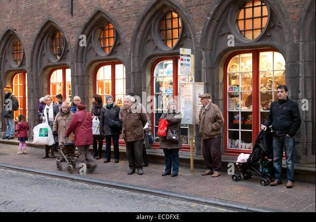 Belgian people standing at a bus queue, - example of normal everyday life; Bruges, Belgium, Europe - Stock-Bilder
