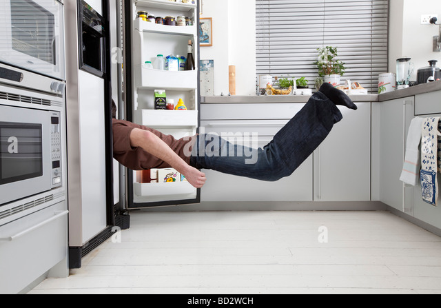 man looking in fridge - Stock-Bilder