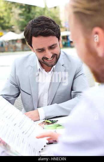 Businessmen deciding menu at sidewalk cafe - Stock Image