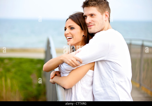 Portrait of a happy couple embracing while in the park - Stock Image