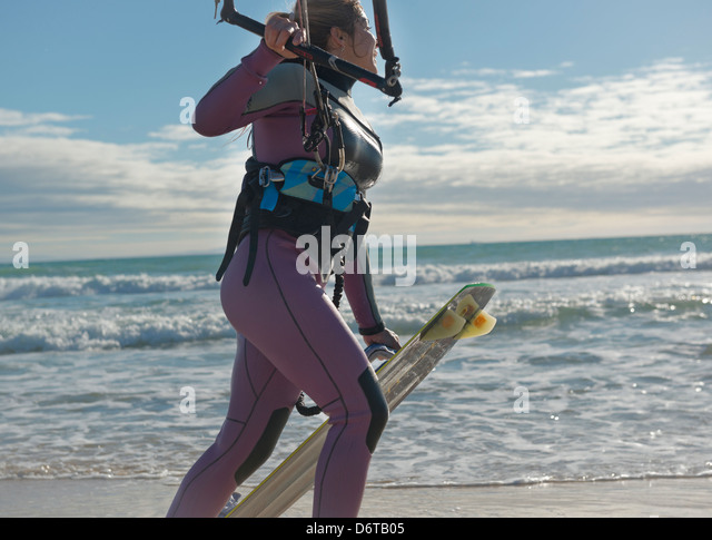 Kitesurfer walking along the beach. Tarifa, Costa de la Luz, Cadiz, Andalusia, Spain, Europe. - Stock Image