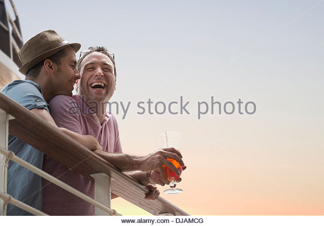 Gay couple having drinks on cruise ship deck - Stock Image