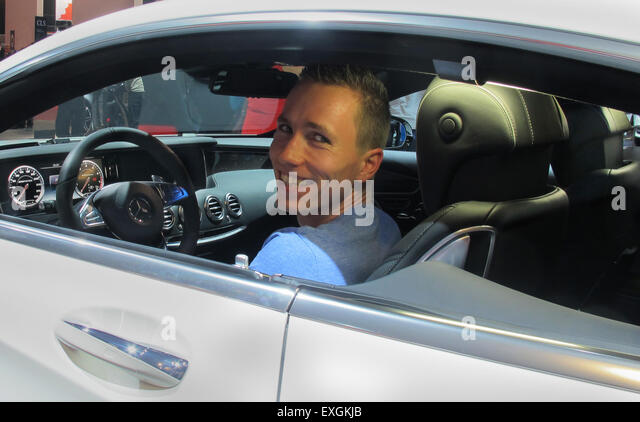 Young visitor poses in Mercedes S class - Stock Image