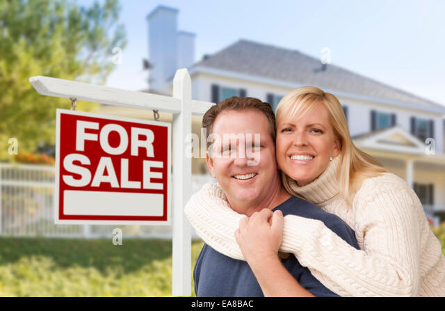 Affectionate Happy Couple in Front of New House and For Sale Real Estate Sign. - Stock Image