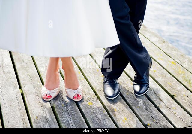 Sweden, Uppland, Arholma, Feet of man and woman standing on wooden pier - Stock Image