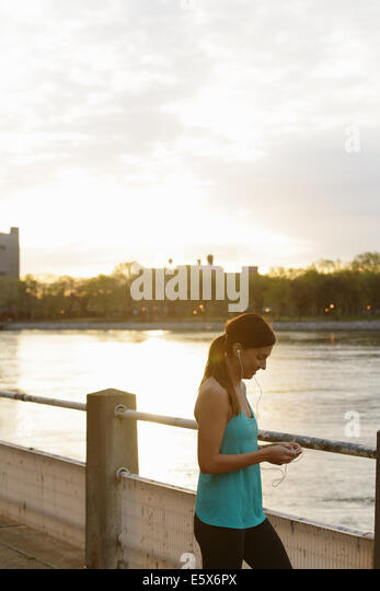 Young female runner on waterfront selecting music for earphones - Stock Image