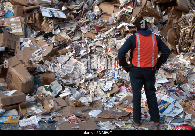 New Jersey Newark recycling center worker paper cardboard trash man pile - Stock Image