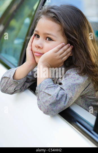 Cute little girl looking out of the car window - Stock Image