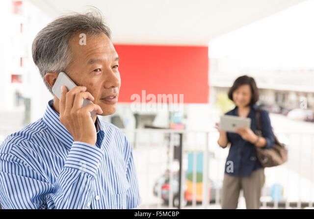 Head and shoulders of mature man talking on smartphone looking away - Stock Image