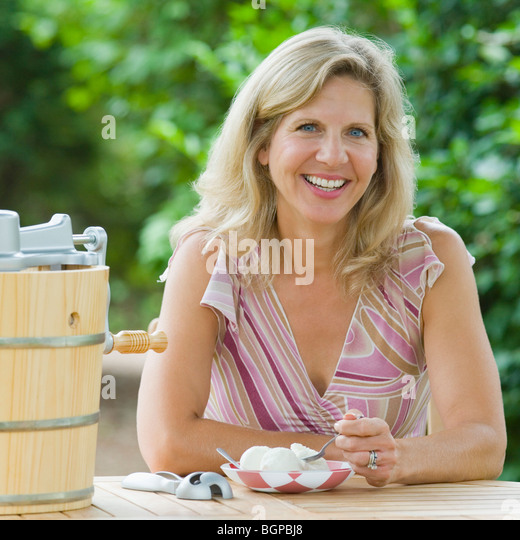Portrait of a mature woman eating an ice cream - Stock Image