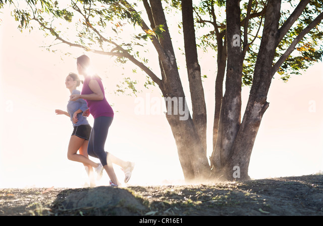 Women running together on dirt path - Stock Image